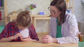 El psicólogo del doctor enseña a un niño autístico a utilizar un smartphone almacen de video