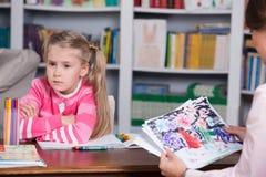 El psicólogo del niño discute el dibujar de una niña Foto de archivo libre de regalías