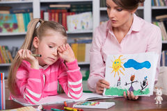 El psicólogo del niño discute el dibujar de una niña fotos de archivo libres de regalías