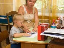 El psicólogo y un niño con Síndrome de Down se realizan Imagenes de archivo