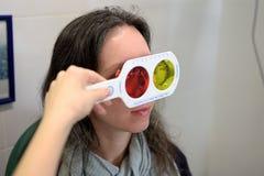 El ?ptico bonito del oftalm?logo del optometrista de la mujer joven realiza una prueba de la acromatopsia imagen de archivo