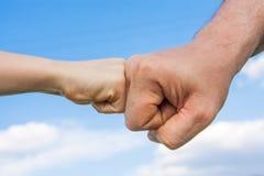 El puño del niño toca el puño masculino contra el cielo Imagenes de archivo