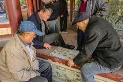El pueblo chino mayor dejó se relaja y jugando a ajedrez chino en el parque ancestral del templo China de la ciudad de Foshan fotos de archivo