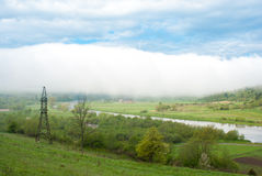 El pueblo debajo de la nube Nube gigante Línea de la transmisión tower Tiempo brumoso Cárpatos, Ucrania Imagenes de archivo