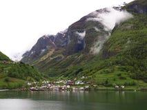 El pueblo minúsculo se acurrucó en un valle de la montaña en el Aurlandsfjord i Fotografía de archivo