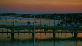 El puente con tráfico rodante y un velero anclado en un río por una ciudad aúllan en la puesta del sol caliente almacen de video