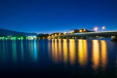 El puente construido a través del río para tomar el coche que corre en la noche con la luz refleja sobre la superficie imágenes de archivo libres de regalías