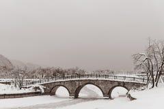 El puente cubrió nieve con el río congelado