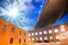 El puente de Brooklyn en Nueva York en la puesta del sol con el underne de los edificios Imagenes de archivo