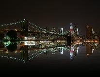 El puente de Brooklyn por noche refleja en el horizonte de East River y de Nueva York Freedom Tower fotos de archivo libres de regalías