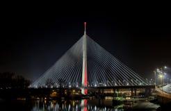 El puente de cable Belgrado en la noche con la ciudad se enciende Foto de archivo