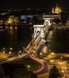 El puente de cadena en Budapest en la noche con la iglesia del ` s de St Stephen Foto de archivo libre de regalías