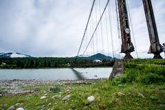 El puente de ejecución sobre el río de Katun es muy viejo Fotos de archivo