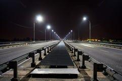El puente de la noche con las linternas, el camino entra la distancia en la noche imágenes de archivo libres de regalías