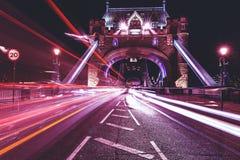 El puente de la torre en Londres en la noche con el semáforo de coche se arrastra imagen de archivo libre de regalías