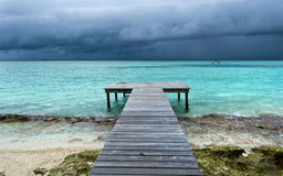 El puente de madera en la playa extendió en el mar Fotos de archivo