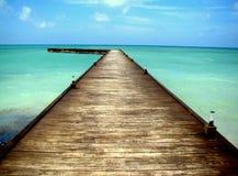 El puente de madera largo termina en el mar azul Imagen de archivo