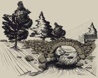 El puente de piedra viejo en las maderas a través del río Imagenes de archivo