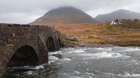 El puente de piedra viejo de Sligachan sobre el río Sligachan con el pico de Beinn Dearg Mhor y de Marsco de las montañas rojas d almacen de metraje de vídeo