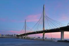 El puente del camino de la carretera del c?rculo sobre el r?o de Neva cerca de la boca de ella sobre la hora azul despu?s de la p fotos de archivo
