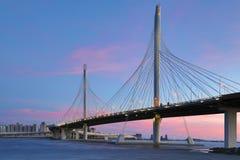 El puente del camino de la carretera del c?rculo sobre el r?o de Neva cerca de la boca de ella sobre la hora azul despu?s de la p imagenes de archivo