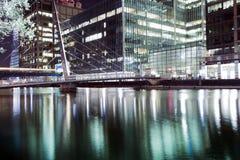 El puente peatonal que conecta Millwall con Canary Wharf bajo noche foto de archivo