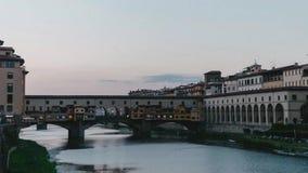 El puente Ponte Vecchioin en Florence Italy durante puesta del sol a partir del día a la noche - time lapse 4K almacen de metraje de vídeo