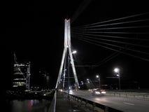 El puente que atraviesa el Daugava del río, distrito financiero de Vansu en el fondo, en la noche, Riga, Letonia Fotografía de archivo libre de regalías