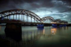 El puente sobre el río con el tren en Riga Letonia por noche fotografía de archivo