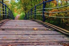 El puente viejo sobre el río invita para un paseo lento en el parque del otoño Fotos de archivo
