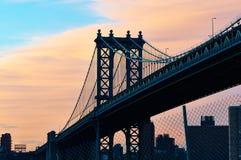 El puente y el horizonte de Manhattan siluetean la visión desde Brooklyn en la puesta del sol Fotos de archivo