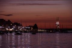 El puerto de Cowes después de la puesta del sol, noche se enciende en hogares y Fotos de archivo libres de regalías