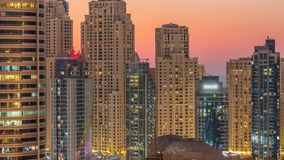 El puerto deportivo de Dubai y día del panorama de los twers de JBR a las luces del timelapse de la noche se giran metrajes