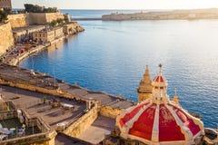 El puerto viejo de La Valeta con el tejado en la salida del sol - Malta de la iglesia Imagen de archivo