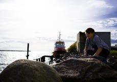 El puerto viejo muchacho del adolescente que se sienta en la playa y las miradas una nave Imagenes de archivo