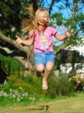 El pulgar encima del niño salta fotografía de archivo
