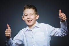 El pulgar feliz acertado de la demostración del muchacho del retrato del primer para arriba aisló el fondo gris foto de archivo libre de regalías