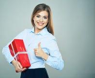 El pulgar feliz de la demostración de la mujer para arriba, sostiene la caja de regalo roja Mujer de negocios po fotografía de archivo libre de regalías