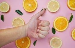 El pulgar para arriba en el limón anaranjado deja el modelo de la fruta cítrica en Backgroun rosado Imagenes de archivo