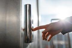 El pulgar presiona el botón del elevador, una mano que alcanza para el botón, el elevador que espera de la muchacha para, comienz Fotos de archivo
