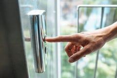 El pulgar presiona el botón del elevador, una mano que alcanza para el botón, el elevador que espera de la muchacha para, comienz Imágenes de archivo libres de regalías