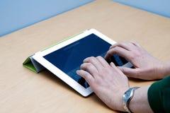 El pulsar de las manos del utilizador de la tablilla de IPad 2 Imagen de archivo libre de regalías
