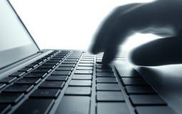El pulsar en el teclado de la computadora portátil. Fotografía de archivo libre de regalías
