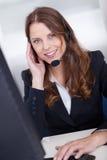 El pulsar que se sienta sonriente del trabajador del centro de atención telefónica Imágenes de archivo libres de regalías