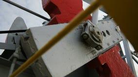 El pumpjack grande de la visión inferior extrae el petróleo crudo en campo almacen de metraje de vídeo