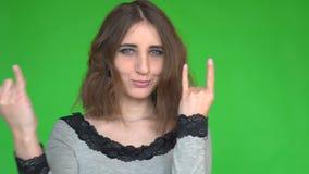 El punky no está muerto Mujer joven fresca atractiva que hace gesto de mano de la muestra del cuerno sobre fondo verde metrajes