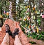 El punto de vista de un caminante que descansa en una hamaca en un camping con las boyas que cuelgan en los árboles en el rastro  imagenes de archivo
