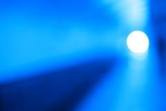 El punto que brilla intensamente diagonal con el azul enciende el fondo del bokeh Imagenes de archivo