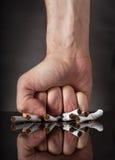 El puño del hombre que machaca los cigarrillos Fotografía de archivo libre de regalías