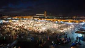 EL quadrato famoso Fna di Jemaa occupato con molte gente e luci durante la notte, Medina di Marrakesh, Marocco immagini stock